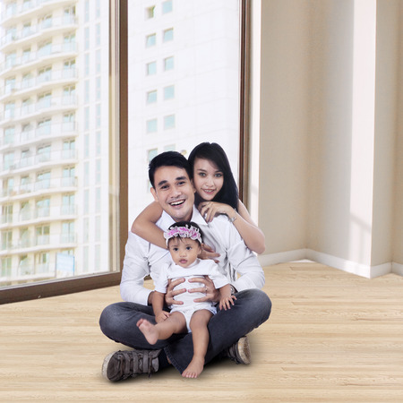 Portrait of happy mother and father with little baby sitting on the new apartment Stock Photo