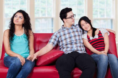 ungeliebt: Frau, die H�nde mit einem Mann, der in der N�he seiner Freundin auf dem Sofa sitzen Lizenzfreie Bilder