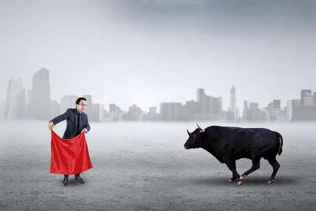 toro: Joven empresario utilizando un trapo rojo para hacer frente a toro furioso, que simboliza la estrategia empresarial Foto de archivo