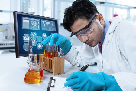 Portrait of young scientist writes the report of observation result on the clipboard, shot in the laboratory Standard-Bild