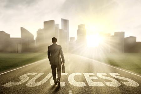 Terug bekijken mannelijke manager met aktetas lopen op de weg naar succes in de ochtend Stockfoto