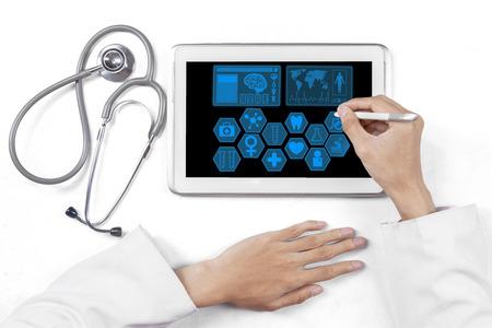 Close-up van de arts handen met behulp van een stylus pen om medische symbool te raken op het tablet