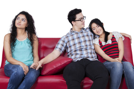 Beautiful young woman holding hands with men sitting near his girlfriend photo