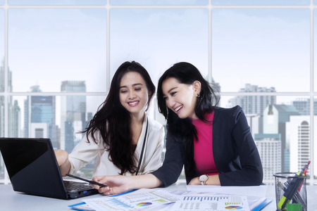 Joyful female workers discussing with laptop on the table near the window at office Stock Photo