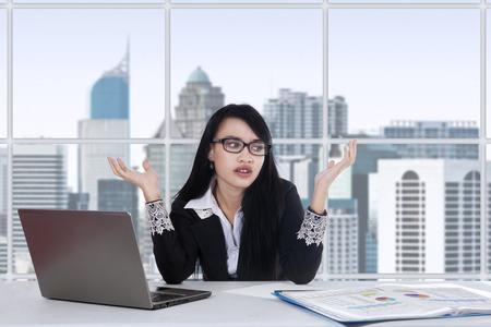 confundido: Trabajadora asi�tica joven que hace su trabajo en la oficina y se ve confundido