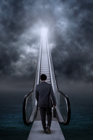 Rear view of businessman carry a briefcase and climbing a stair of hope to the sky photo