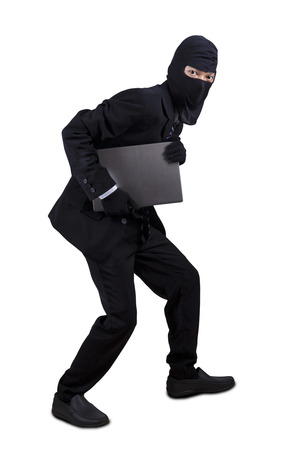 Full length of businessman with mask stealing a laptop computer, isolated on white