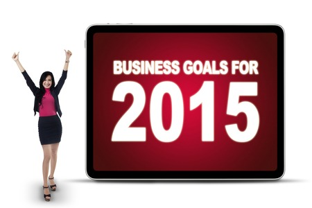 Portrait of happy businesswoman standing near a board with a text of business goals for 2015 photo