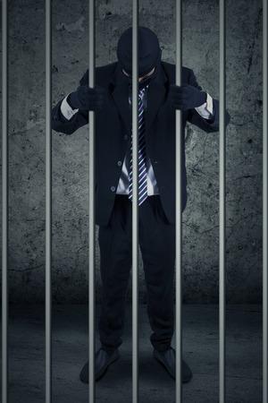 Niezadowolony biznesmen z maski stojących wewnątrz więzieniu jako więzień Zdjęcie Seryjne