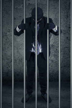 culpable: Unhappy businessman with mask standing inside the jail as the prisoner