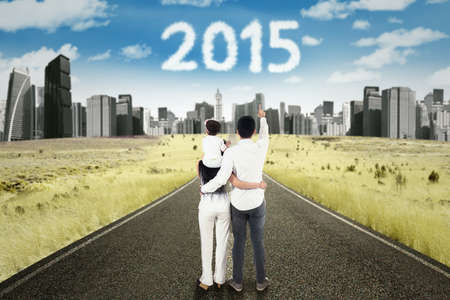 better chances: Back view of happy family standing on the road while pointing at numbers 2015 over the city Stock Photo