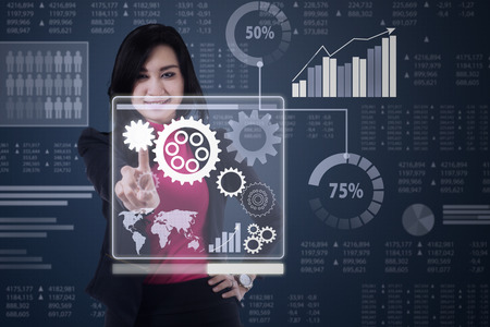 operate: Pretty businesswoman using a virtual screen to operate business gear with financial background Stock Photo