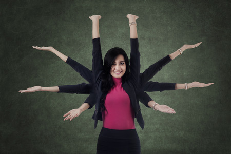 multi tasking: Portrait of beautiful businesswoman smiling at the camera while showing eight hands Stock Photo