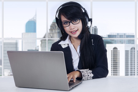 customer service representative: Beautiful woman working with laptop while using headset in the office Stock Photo