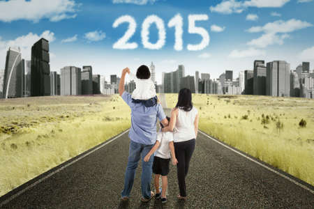 better chances: Four member of happy family walking on the highway toward the city to get better future with numbers 2015 on the sky