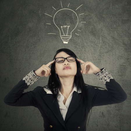 seeking solution: Portrait of beautiful business woman gets solution or idea by thinking under light bulb