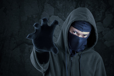 horrifying: Portrait of scary bandit with mask and hoodie try to take something