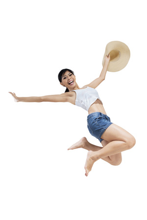 short pants: Portrait of happy woman wearing short pants and enjoy freedom by jumping in the studio