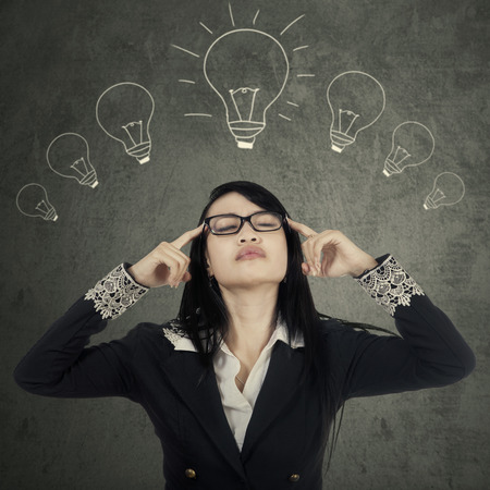 seeking solution: Portrait of female manager seeking inspiration or idea under lightbulbs Stock Photo