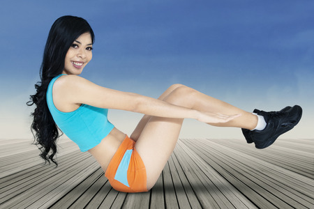 situp: Portrait of healthy woman sitting on the wooden floor while doing sit-up exercise and smiling at the camera