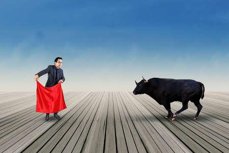 toro: Empresario profesional con un trapo rojo para luchar con un toro al aire libre Foto de archivo