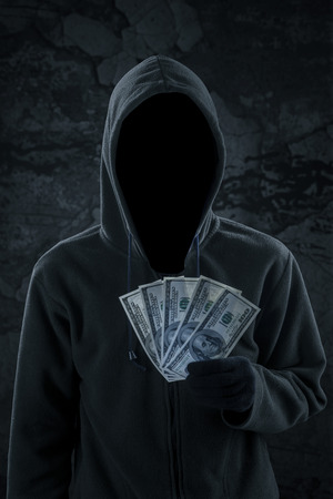 horrifying: Scary robber with hoodie and mysterious face holds dollar cash