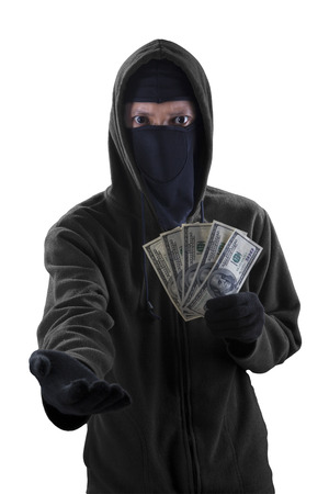 forcing: Male burglar wearing mask and holding money dollar while forcing someone to give money