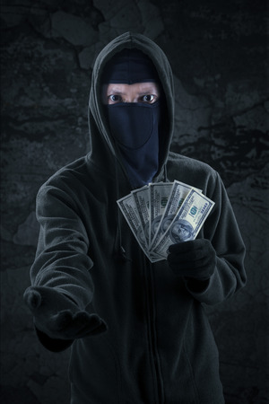 horrifying: Male criminal wearing mask and hoodie taking money dollars from someone