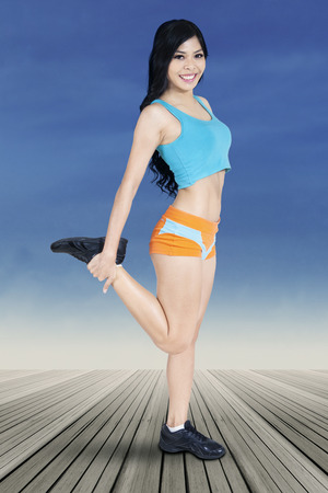 warm up: Beautiful woman smiling at the camera while doing warm up on her legs muscle