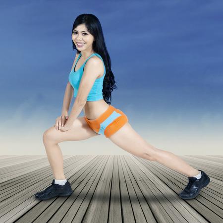 warm up: Giovane donna asiatica facendo allenamento e scaldare le gambe muscoli, girato all'aperto sotto il cielo blu Archivio Fotografico