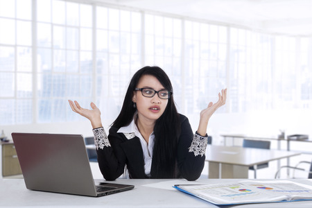 seeking solution: Young businesswoman looks confused in the office while working with laptop computer