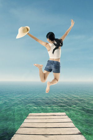 short pants: Rear view of attractive woman with short pants jumping on the pier at tropical beach