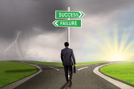 business success: Male worker walking on the road and find two signpost with two choices to success or failure