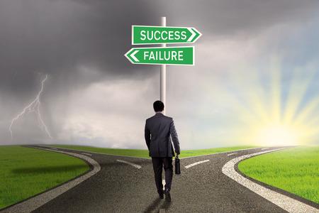 Mannelijke werknemer die op de weg en vind twee wegwijzer met twee keuzes voor het succes of falen