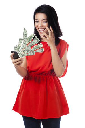 coming out: Shocked young woman looking money cash coming out from her mobile phone Stock Photo