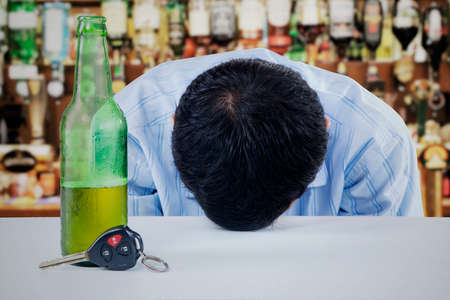 Young man drunk with bottle of beer and key on the table of bar photo