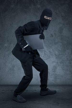 Male worker wearing mask sneaking to steal a laptop computer