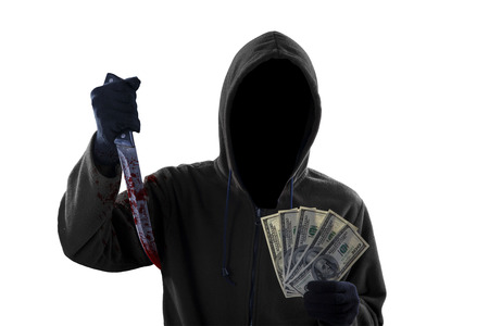 Mysterious mugger wearing black hoodie while holding a bloody knife and money dollar photo