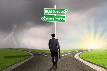 Empresario con maletín caminando en el camino y obtener dos opciones de la decisión correcta o decisión equivocada