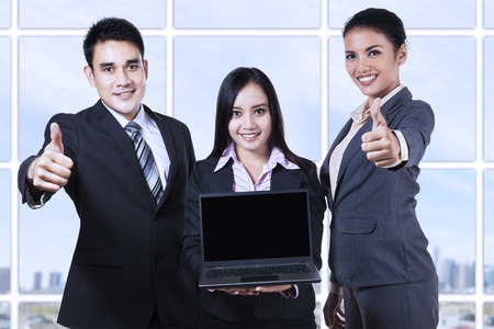 Asian business team showing blank screen on laptop and thumbs up photo