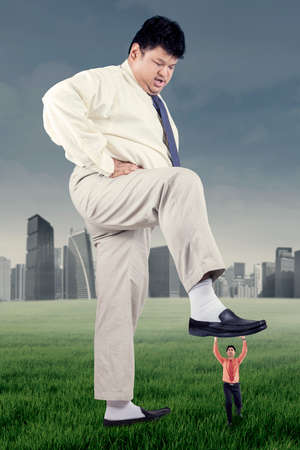 trample: Business competition concept with big businessman trample a little entrepreneur