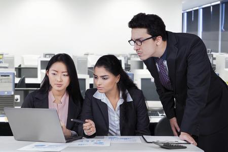 jovenes empresarios: Grupo de empresarios jóvenes, reunión con la computadora portátil y el papeleo en el lugar de trabajo Foto de archivo