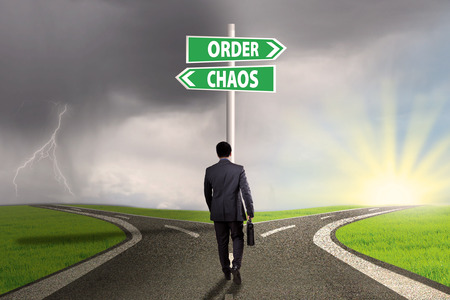 order chaos: Rear view of businessman walking on the road with two choices to the right way or chaos
