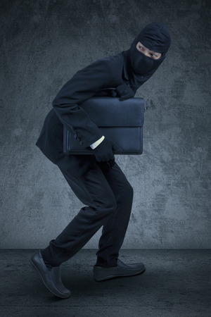 Male entrepreneur wearing a mask and slink to steal a briefcase, shot against dark background