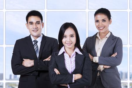 ejecutivos: Hombres de negocios confidentes que miran a la cámara sonriendo
