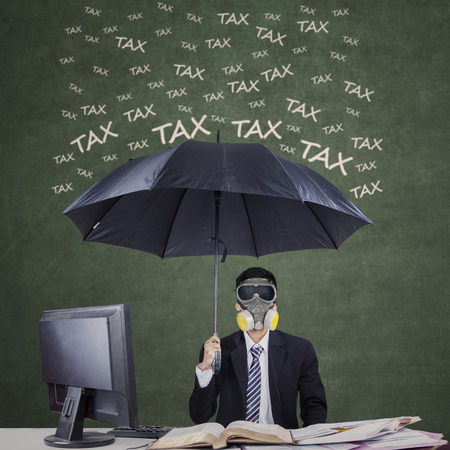 Businessman wearing a gas mask and umbrella to protect him from tax Stockfoto