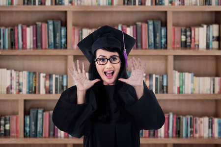grad: Excited female grad shouting happily in the library