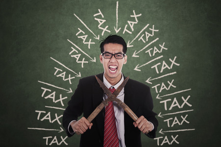 taxation: Stressful businessman having tax problems and try to cut his neck