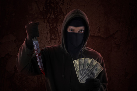 murderer: Scary murderer showing bloody knife while holding money cash
