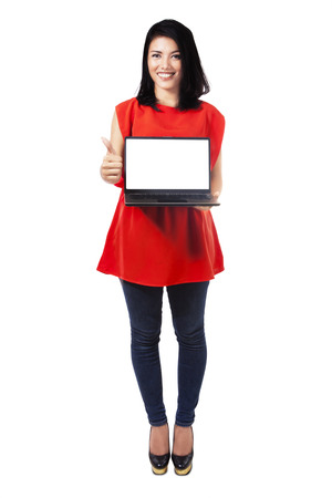 laptop stand: Full length of young woman showing thumb up while holding laptop with blank screen, isolated on white